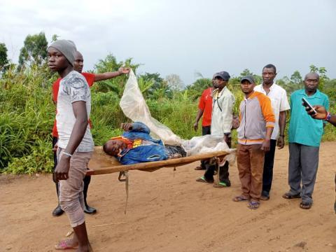 Plusieurs personnes portant un corps dans un brancard à Halungupa.